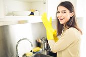 Hand cleaning.Young housewife woman washing dishes in kitchen.Preparing to clean poster