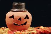 foto of jack-o-laterns-jack-o-latern  - A pumpkin sits in a pile of fallen leaves - JPG