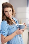 Attractive young female drinking tea at home, standing at wall.?