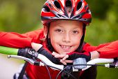 Close-up of a little boy?s face on bike looking at camera and smiling