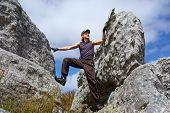 Young Man Climbs On Rock