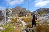 Young Hiker Stands In Front Of Mountain Chalet