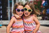 Identical Twin Girls On Summer Vacation Posing For Camera. poster