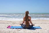Woman Doing Yoga Exercise On Beach In Half Lotus Pose Or Ardha Padmasana