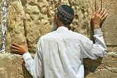 JERUSALEM - AUG 18: Unidentified person praying at Western Wall aka Wailing Wall during Tisha B'Av fast day before major celebrations of Jewish New Year on August 18, 2004 in Jerusalem, Israel.