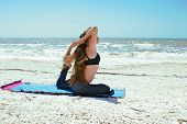 Young Woman Doing Yoga Exercise On Beach In Kapotasana Or Pigeon Pose