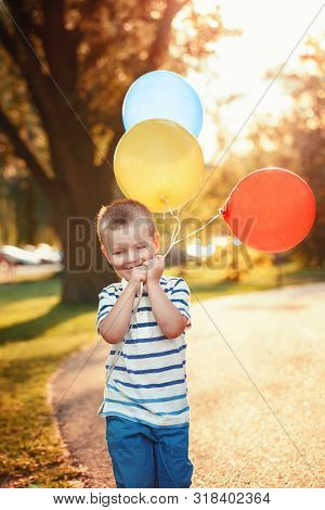 poster of Cute Adorable Little Caucasian Boy Toddler Child With Colorful Balloons In Park Outdoor. Kid Enjoyin