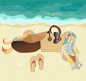 Summer at the Beach - stylish accessories on golden sand, at the beach: summer hat, straw bag, flip flops, sunglasses and colorful silk scarf or sari