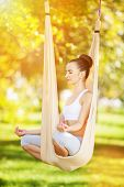 Anti-gravity Yoga outdoor. Happy woman doing yoga exercises, meditate in sunny park. Yoga meditation poster