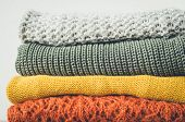 Pile Of Knitted Woolen Sweaters Autumn Colors On Wooden Table. Clothes With Different Knitting Patte poster