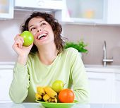 Dieting concept. Healthy Food .Diet. Laughing Young Woman Eats Fresh Fruits