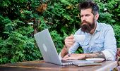 Book Apartment Online. Man Bearded Hipster Sit Outdoors With Laptop Surfing Internet And Drinking Co poster