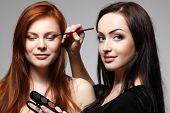 Retrato da bela jovem ruiva com esteticista fazendo maquiagem olhos sombra