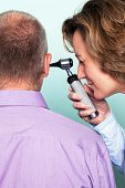 Photo of a female doctor examining a patients ear using an otoscope.