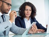 Business Colleagues Analyzing Digital Reports On Tablet And Laptop. Business Man And Woman Sitting A poster