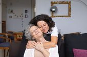 Mother And Daughter With Closed Eyes Hugging. Happy Senior Mother And Middle Aged Daughter Hugging T poster