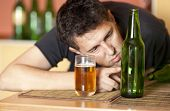 Bêbado.  Homem bebendo uma cerveja. Concentrar-se na garrafa