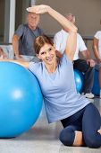 Smiling woman doing back exercises with gym ball in fitness center