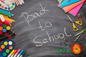 Stationery accessories on background of school blackboard with inscription: Back to school. Top view poster