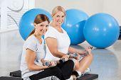 Two elderly women exercising with dumbbells on gym mats in fitness center