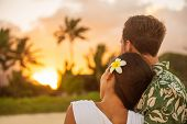 Romantic couple relaxing watching sunset on beach stroll view from back. Woman resting head on lover poster