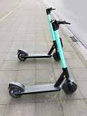Two Electric Kick Scooters Or E-scooter Parked On Sidewalk - E-mobility Or Micro-mobility Trend poster