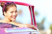 Car woman happy in old pink retro vintage car. Young woman driving on road trip on beautiful sunny s
