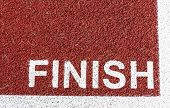 Bold Text Finish Is Painted At The Finish Line On A Red Track In White. poster