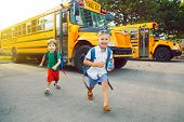 Two Funny Happy Caucasian Boys Students Kids Running Near Yellow Bus On 1 September Day. Education A poster