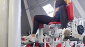 A Woman In Leggins Training In The Gym - Training Her Legs On The Butterfly Training Apparatus poster