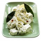 Dish of creamy marinated feta cheese with bay leaves and preserved lemon.  Isolated on white.