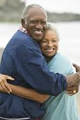image of early 60s  - Mature Couple Hugging on Beach - JPG