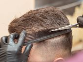 Males Hair Cutting With Comb And Scissors, Close Up View. Hairstylists Hands In Black Rubber Gloves  poster