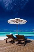 picture of infinity pool  - Deck chairs and infinity pool over blue tropical lagoon - JPG