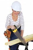 Woman using a handsaw