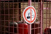 The Sign Prohibiting Smoking Is Hanging On The Fence Of The Warehouse With Gas Or Oxygen Cylinders.  poster