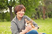 Portrait Of Cute Happy Mature Woman With Puppy Dog Pet In Summer Park poster