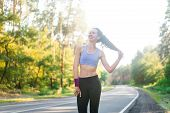 Beautiful Young Caucasian Girl Standing On Asphalt Forest Road Smiling Before Jogging. Athlete Befor poster