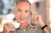 Grey haired man drinking coffee and speaking on mobile telephone