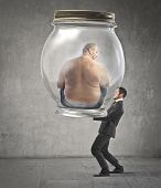 Businessman carrying a jar with an obese man in it