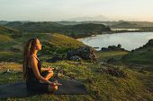 Woman Doing Yoga Alone At Sunrise With Mountain And Ocean View. Harmony With Nature. Self-analysis A poster