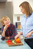 stock photo of mums  - Mother and son preparing food in domestic kitchen - JPG