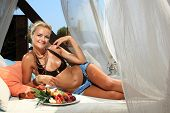 Young smiling woman with fruits salad in the summertime