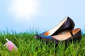 Photo of womens high heel shoes and a mobile phone on grass against a bright blue sky with sunshine.