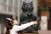 japanese lolita hugging cat statue in Tokyo