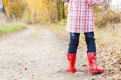 detail of little girl wearing rubber boots in autumn
