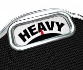 The word Heavy on the display of a scale in close-up, measuring weight or mass to determine if you a