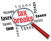 A magnifying glass hovering over the word tax breaks, symbolizing the advice and tricks that an acco
