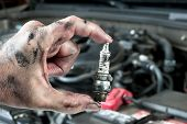 An auto mechanic holds an old, dirty spark plug over a car engine he is tuning up.