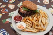 Kofta Burger with fries on colorful tile table